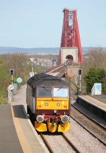 A West Coast Railways class 47 diesel waits for a green signal to head onto the Forth Bridge in pursuit of the railtour