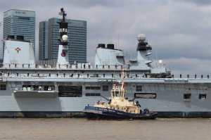 HMS Illustrious with Svitzer Bootle, one of the four tugs assisting her passage