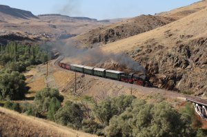 TCDD 56 548 steams towards us, with a distant view of the mountain village of Akköy on the canyon rim